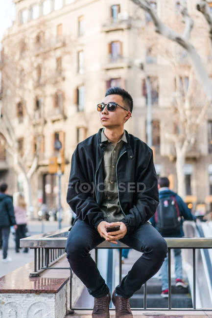 Man in trendy outfit and sunglasses sitting on fence at street scene — Stock Photo