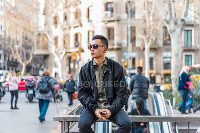 Man in trendy outfit and sunglasses sitting on street — Stock Photo