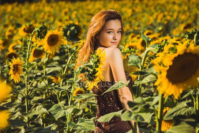 Jolie jeune femme posant sur le champ de tournesols et regardant par-dessus l'épaule à la caméra . — Photo de stock