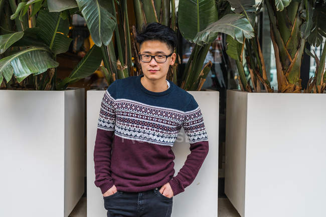 Young stylish man in glasses posing by potted plants — Stock Photo