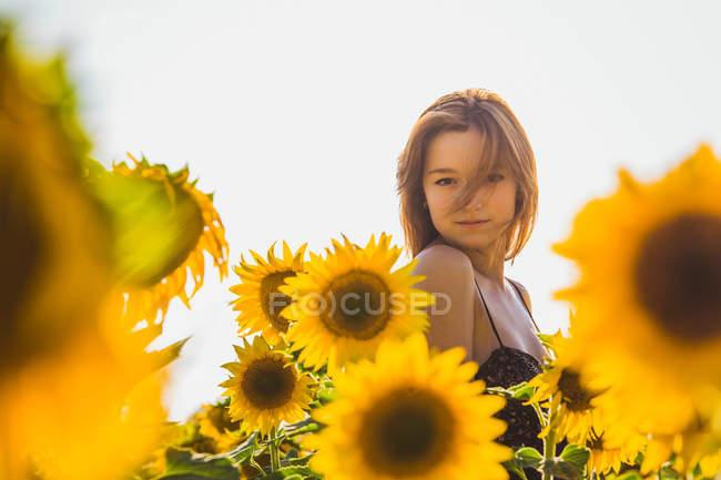 Довольно молодая женщина, стоя в подсолнухах и глядя на камеру — стоковое фото