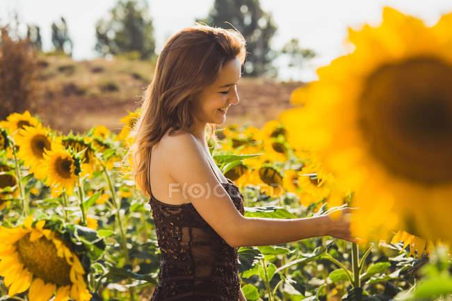 Вид сбоку улыбается женщина в подсолнухах — стоковое фото