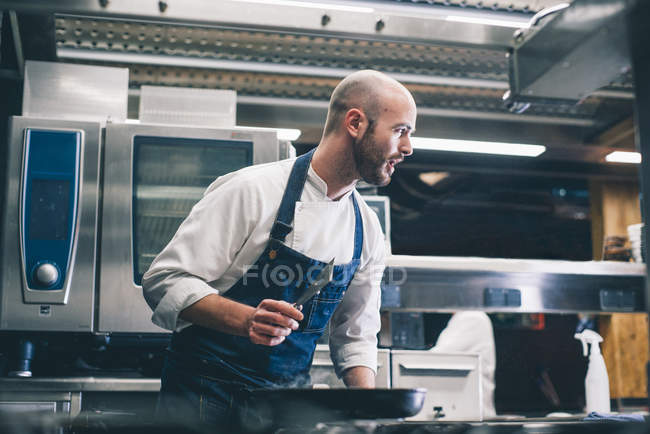 Cook bending over stove in restaurant kitchen — Stock Photo
