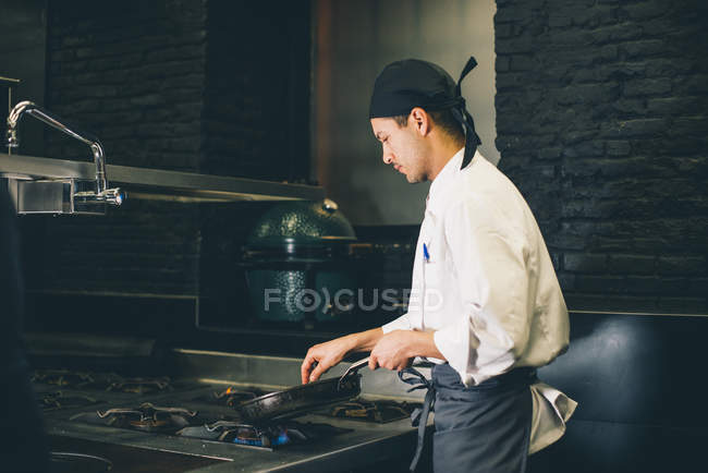 Cook frying meat on pan at stove — Stock Photo