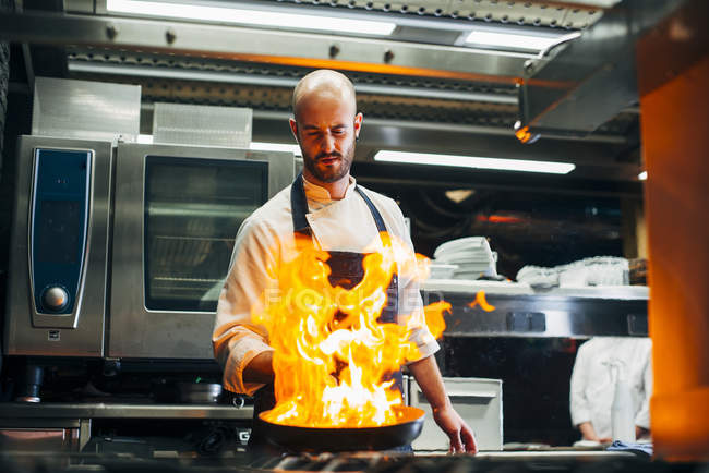 Chef standing in restaurant kitchen and making flambe on frying pan. — Stock Photo