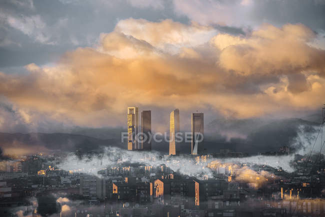 Vista a distanza dei grattacieli avvolti in scenografici paesaggi nuvolosi al tramonto — Foto stock