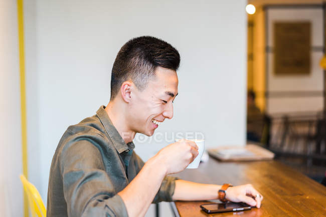 Smiling young man drinking coffee — Stock Photo