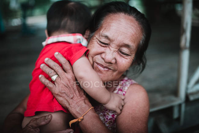 LAOS, 4000 ISLANDS AREA: Cheerful grandmother holding child on hands — Stock Photo