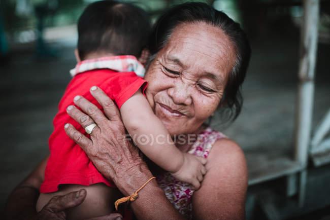 ЛАОС, 4000 ОСТРОВ АРЕЯ: Веселая бабушка держит ребенка на руках — стоковое фото