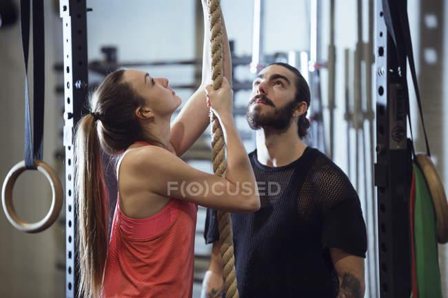 Uomo adulto e donna che appendono sulla corda mentre ti alleni in palestra — Foto stock