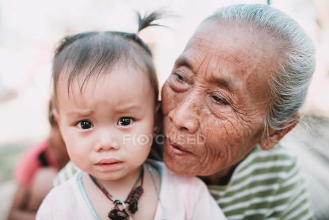 Nong khiaw, laos: Seniorin umarmt reizendes Mädchen mit traurigem Gesicht. — Stockfoto