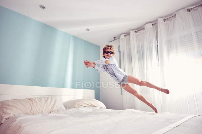 Cheerful young boy having fun and jumping on bed at home. — Stock Photo