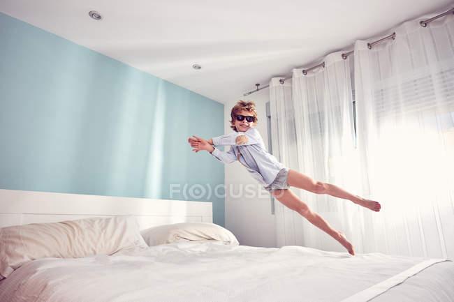 Веселий хлопчика весело і стрибати на ліжку у себе вдома — стокове фото