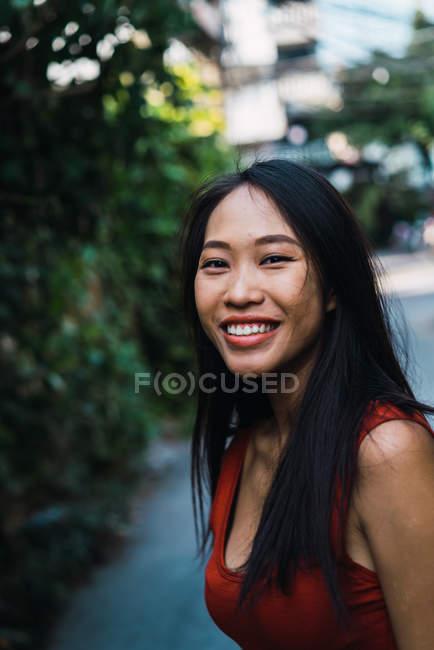 Fröhliche junge Frau blickt auf Straßenszene in die Kamera — Stockfoto