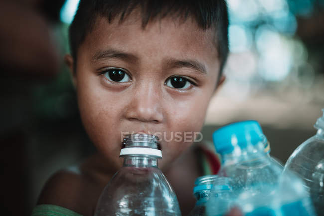 LAOS, 4000 ILHAS ÁREA: Menino água potável de garrafa de plástico e olhando para a câmera . — Fotografia de Stock