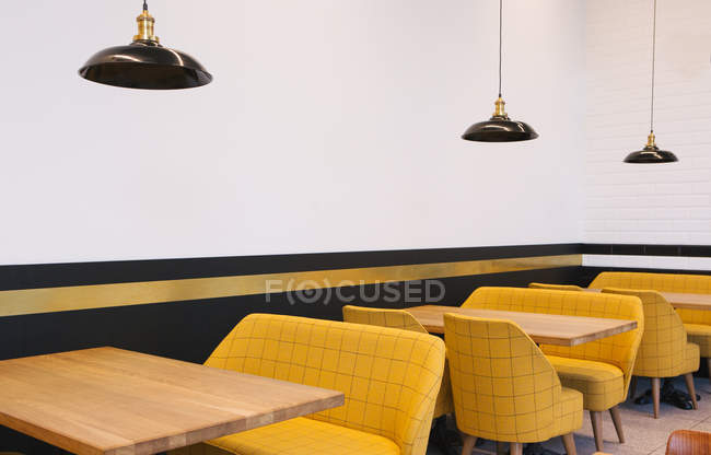 Interior view of tables and yellow chairs in cafe — Stock Photo