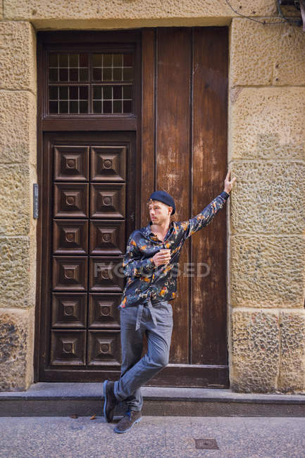 Young man with cup leaning on old wall and looking away on street. — Stock Photo
