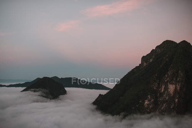 Thick clouds floating at peaks of high mountains in dusk — Stock Photo