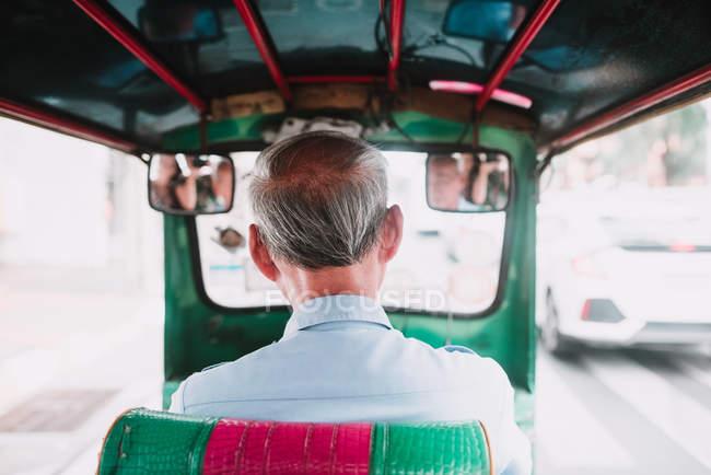 Back view of unrecognizable senior man driving rickshaw on city street. — Stock Photo