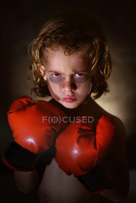 Милый уверенный в себе малыш в бинтах и боксёрских перчатках смотрит в камеру. — стоковое фото