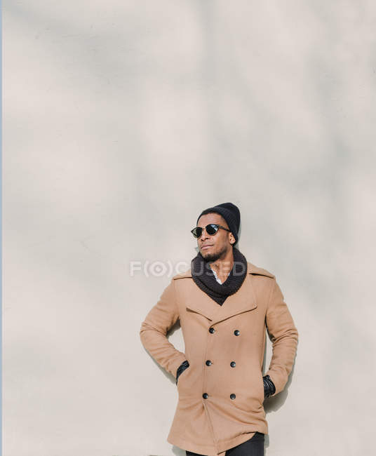 Stylish man in sunglasses and coat leaning on wall — Stock Photo