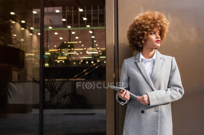 Stylish woman in gray coat standing with digital tablet on street and looking away. — Stock Photo