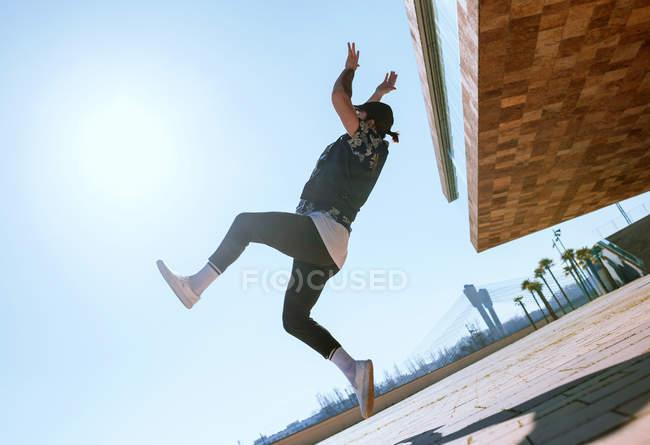 Вид сбоку до неузнаваемости человека, выполняя трюк backflip в Солнечный день. — стоковое фото