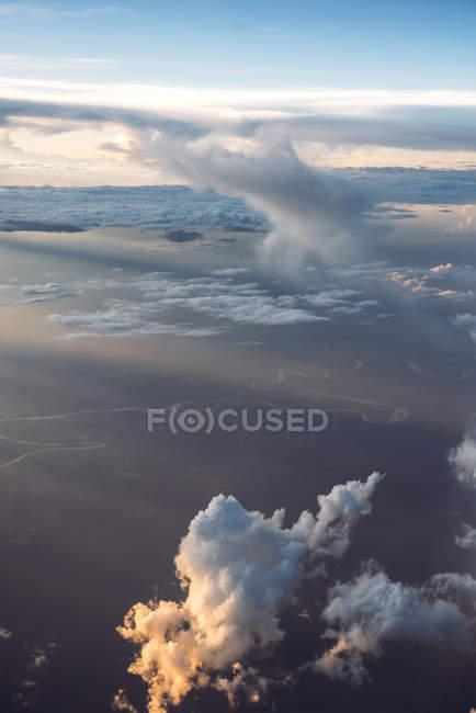 Аэрофотоснимок облаками и землей в закат огни — стоковое фото