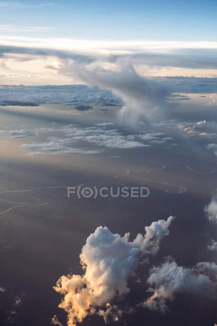 Aerial view to clouds and ground in sunset lights. — Stock Photo