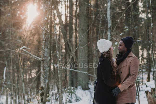 Vielrassige Paarbeziehung im Winterwald bei sonnigem Tag — Stockfoto