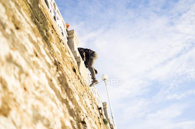 Mann im bewölkten Tag an alte raue Wand Klettern. — Stockfoto