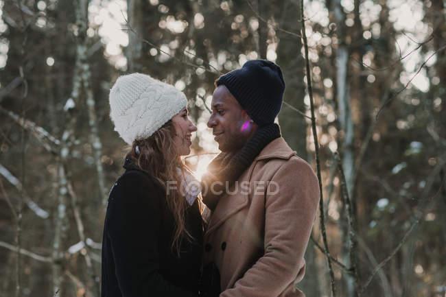 Подсветка многорасовых пар в зимнем лесу — стоковое фото