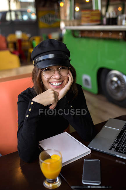 Stylish woman sitting at laptop and notebook in cafe — Stock Photo