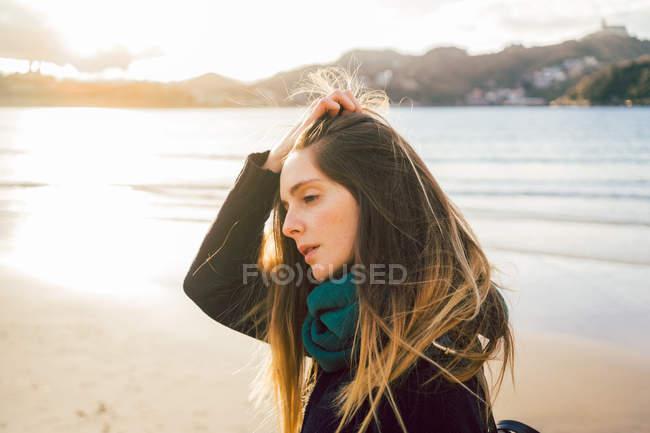 Verträumtes Mädchen, das am Sandstrand steht und Haare berührt — Stockfoto