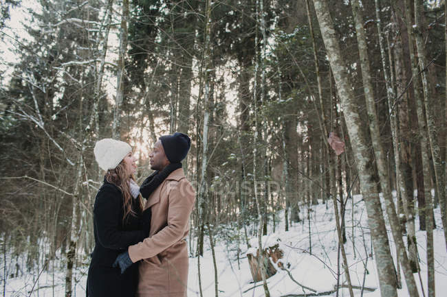 Romantic multiracial couple embracing in winter forest — Stock Photo