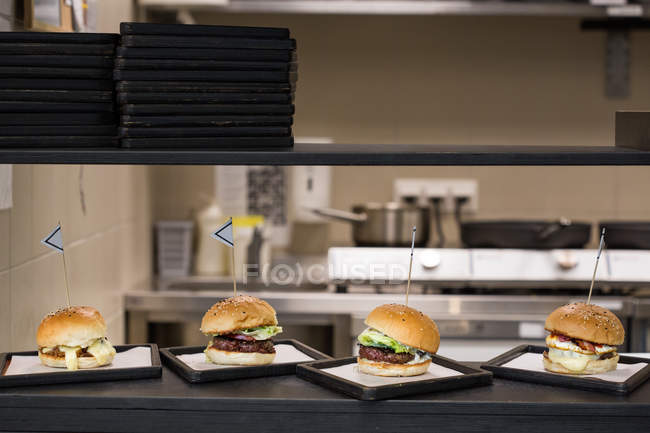 Tasty appetizing burgers served on plates on kitchen of restaurant. — Stock Photo
