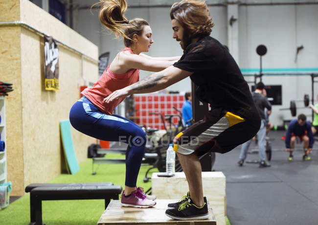 Side view of sporty couple jumping while training in gym. — Stock Photo