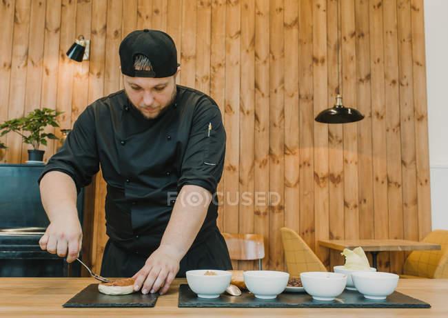 Uomo in piedi e mettendo la salsa sul panino mentre cucinare hamburger sul tavolo di caffè del cuoco. — Foto stock