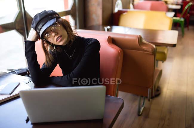 Mujer con estilo que se apoya en la mano en el ordenador portátil en la cafetería - foto de stock