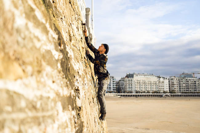 Seitenansicht eines Mannes, der an bewölkten Tagen auf eine alte raue Wand klettert. — Stockfoto