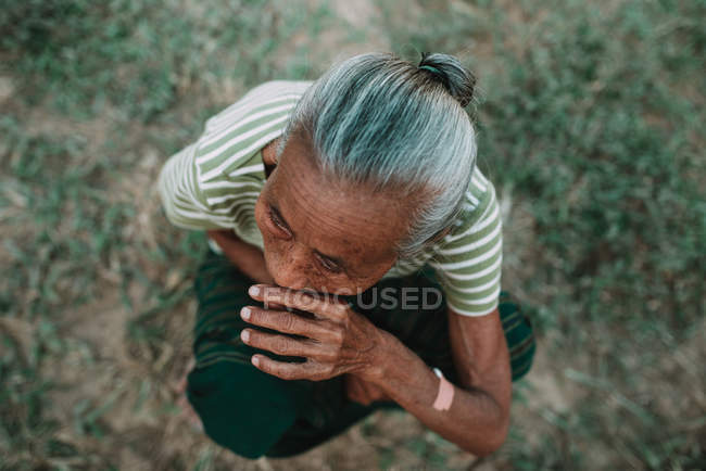 NONG KHIAW, LAOS:From above shot of mature local woman sitting on ground. — Stock Photo