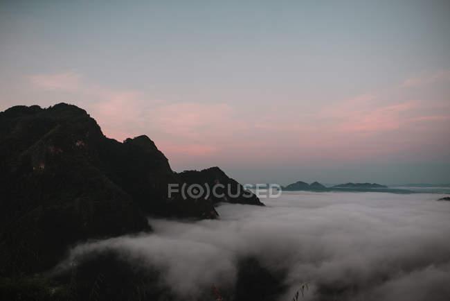 Nuages près des sommets au coucher de soleil crépuscule — Photo de stock