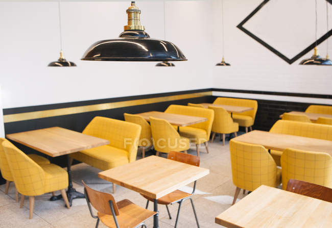 Empty wooden tables and yellow chairs in cafe — Stock Photo