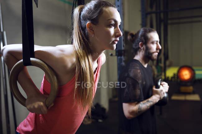 Vista lateral de hombre y mujer deportistas haciendo ejercicio en el gimnasio . - foto de stock