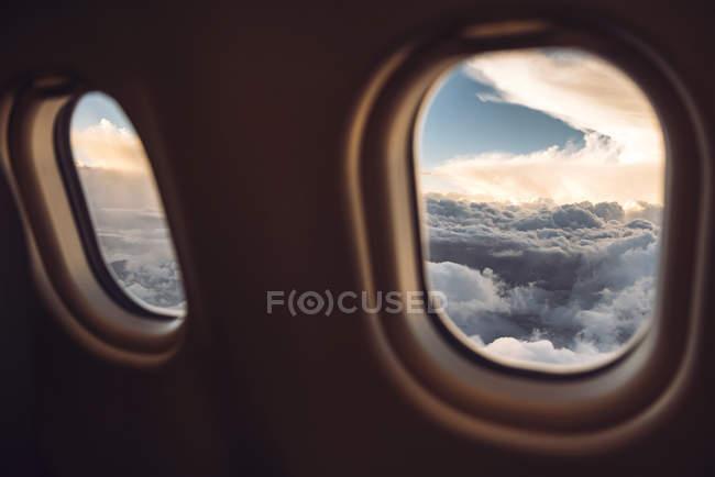 Ve a cloudscape escénica a través de la ventana de avión. - foto de stock
