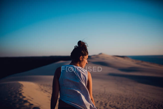 Rear view of woman standing on sand dunes and looking away. — Stock Photo