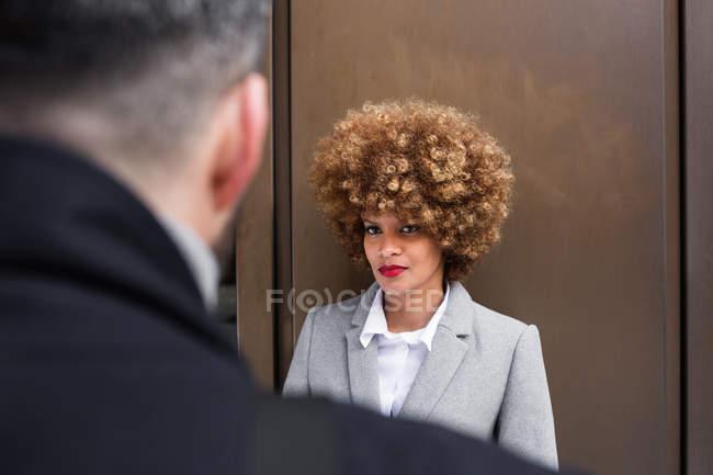 Через плечо зрения вдумчивый стильной женщины, глядя на человека — стоковое фото