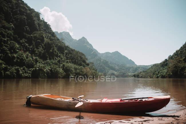 Commandes de canoë en bois à la rive de la rivière qui traverse les montagnes — Photo de stock