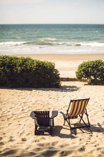 Two empty loungers placed on sunny sandy beach at ocean. — Stock Photo