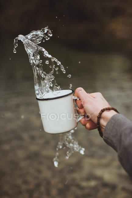 Cultivo mano salpicaduras de agua de la taza de metal en la naturaleza . - foto de stock
